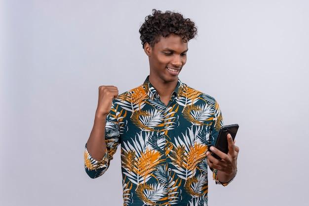 Fröhlicher junger gutaussehender dunkelhäutiger mann mit lockigem haar im blattbedruckten hemd, das sein smartphone mit geballter faust betrachtet