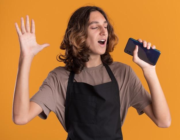 Fröhlicher junger gutaussehender friseur in uniform, der die hand in der luft hält und das mobiltelefon hält, das es als mikrofon singt, mit geschlossenen augen isoliert auf oranger wand
