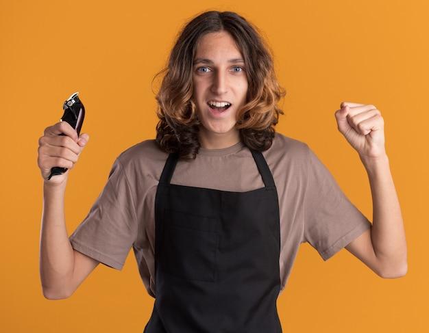 Fröhlicher junger gutaussehender friseur in uniform, der haarschneidemaschinen hält und nach vorne schaut und die ja-geste isoliert auf oranger wand macht