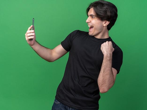 Fröhlicher junger gutaussehender kerl mit schwarzem t-shirt, der das telefon hält und anschaut und die ja-geste einzeln auf grüner wand zeigt