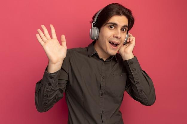 Fröhlicher junger gutaussehender kerl mit schwarzem t-shirt mit kopfhörern, die hallo-geste einzeln auf rosa wand zeigen