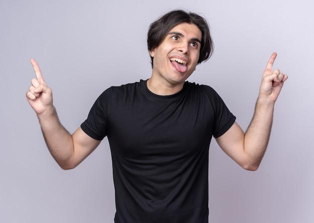 Fröhlicher junger gutaussehender kerl mit schwarzem t-shirt zeigt nach oben die zunge isoliert auf weißer wand