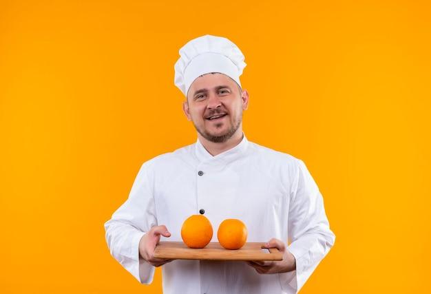 Fröhlicher junger gutaussehender koch in kochuniform mit schneidebrett mit orangen darauf isoliert auf oranger wand