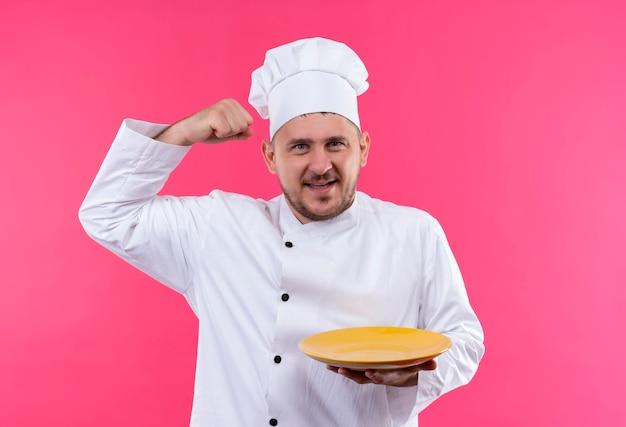 Fröhlicher junger gutaussehender koch in kochuniform mit teller, der stark isoliert auf rosa wand gestikuliert