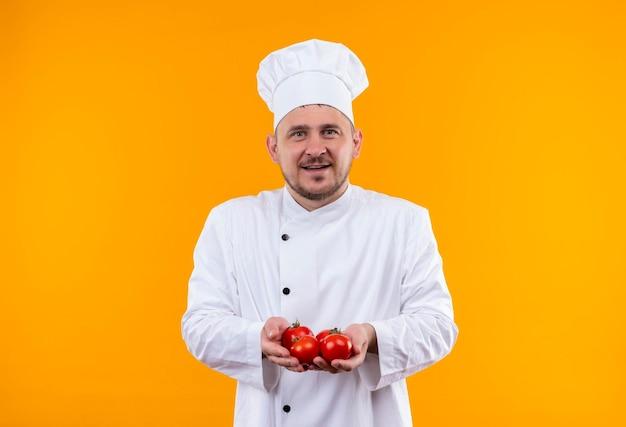 Fröhlicher junger gutaussehender koch in kochuniform mit tomaten isoliert auf oranger wand