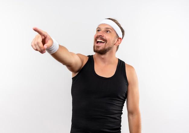 Fröhlicher junger, gutaussehender, sportlicher mann mit stirnband und armbändern, der auf die seite zeigt und auf die weiße wand mit kopienraum blickt