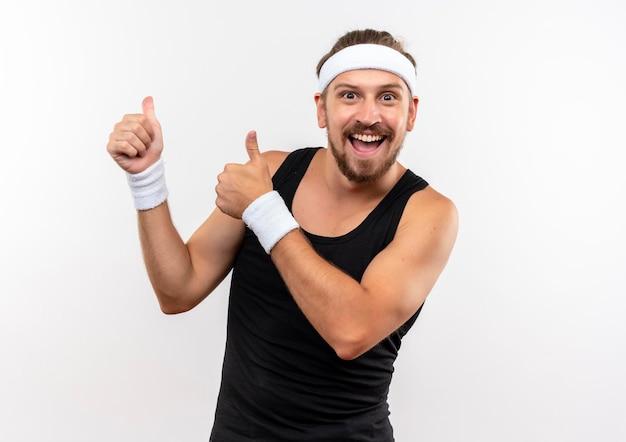 Fröhlicher junger, gutaussehender, sportlicher mann mit stirnband und armbändern, der daumen nach oben zeigt, isoliert auf weißer wand mit kopierraum