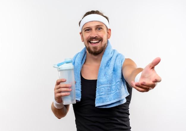 Fröhlicher junger, gutaussehender, sportlicher mann mit stirnband und armbändern, der eine wasserflasche hält und die hand isoliert auf weißer wand ausstreckt