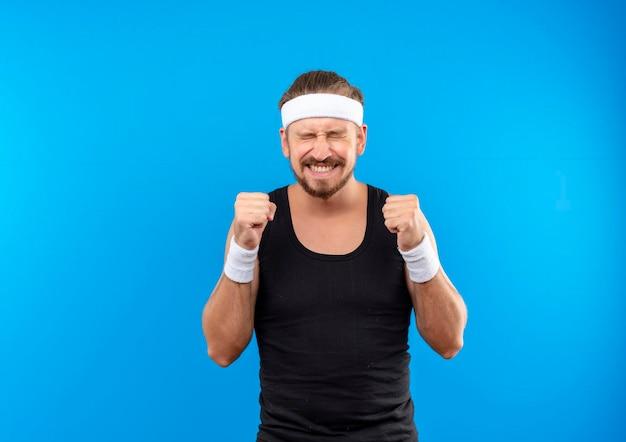 Fröhlicher junger, gutaussehender, sportlicher mann mit stirnband und armbändern, der fäuste mit geschlossenen augen zusammenballt, isoliert auf blauer wand mit kopierraum