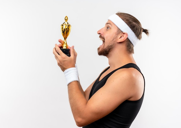 Fröhlicher junger, gutaussehender, sportlicher mann mit stirnband und armbändern, der in der profilansicht steht und siegerpokal isoliert auf weißer wand mit kopierraum hält holding