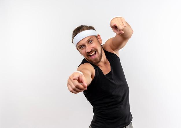 Fröhlicher junger gutaussehender sportlicher mann mit stirnband und armbändern, die isoliert auf weiße wand mit kopierraum zeigen