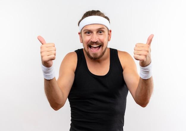 Fröhlicher junger gutaussehender sportlicher mann mit stirnband und armbändern mit daumen nach oben isoliert auf weißer wand