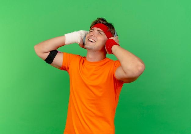 Fröhlicher junger gutaussehender sportlicher mann mit stirnband und armbändern und kopfhörern und telefonarmband mit verletztem handgelenk, das mit verband umwickelt ist, der mit den händen auf kopfhörern aufschaut