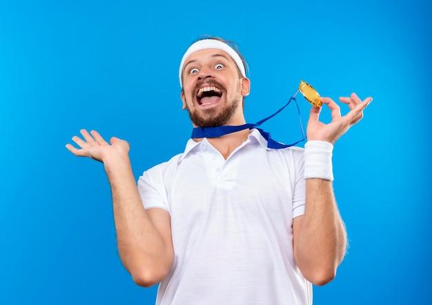 Fröhlicher junger gutaussehender sportlicher mann mit stirnband und armbändern und medaille um den hals, der medaille hält und leere hand einzeln auf blauer wand zeigt