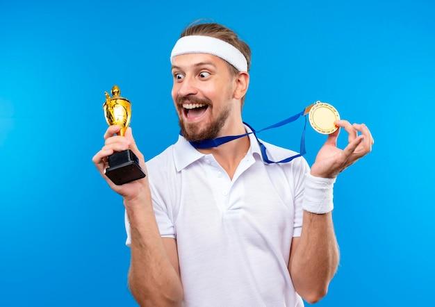 Fröhlicher junger, gutaussehender, sportlicher mann mit stirnband und armbändern und medaille um den hals, der medaille und siegerpokal hält und den pokal einzeln auf blauer wand betrachtet