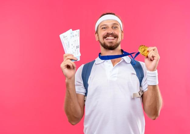 Fröhlicher junger gutaussehender sportlicher mann mit stirnband und armbändern und rückentasche mit medaille um den hals, die medaillen und flugtickets einzeln auf rosafarbener wand mit kopierraum hält