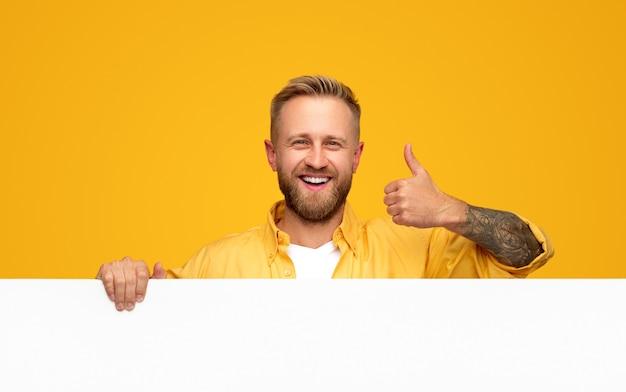 Fröhlicher junger hipster-mann mit tätowierungen und bart, die leeres weißes plakat halten