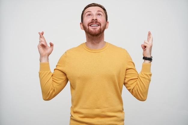 Fröhlicher junger hübscher braunhaariger bärtiger mann mit kurzem haarschnitt, der hände mit gekreuzten fingern hebt und glücklich nach oben schaut, senfpullover tragend