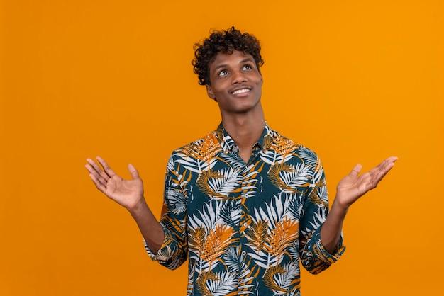 Fröhlicher junger hübscher mann im hemd, der seine arme weit offen öffnet und aufschaut