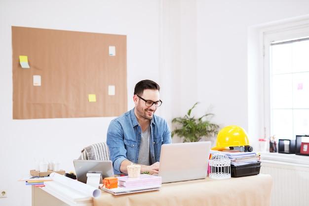 Fröhlicher junger hübscher moderner regisseur, der an einem laptop in seinem großen hellen büro arbeitet.