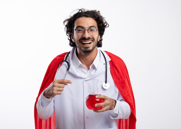 Fröhlicher junger kaukasier in optischer brille mit arztuniform mit rotem mantel und mit stethoskop um den hals hält und zeigt auf rote chemische flüssigkeit in glasflasche
