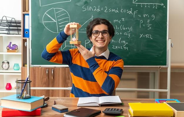 Fröhlicher junger kaukasischer geometrielehrer mit brille am schreibtisch sitzend mit schulwerkzeugen im klassenzimmer mit sanduhr hour