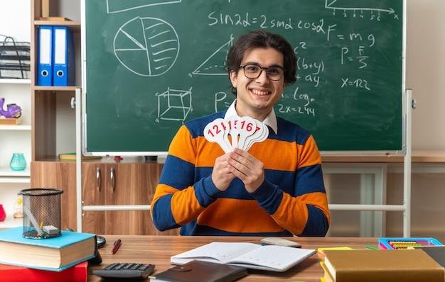 Fröhlicher junger kaukasischer geometrielehrer mit brille, der am schreibtisch mit schulmaterial im klassenzimmer sitzt und zahlenfans zeigt, die nach vorne schauen