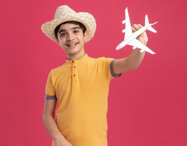Fröhlicher junger kaukasischer junge, der strandhut trägt und flugzeugspielzeug hält