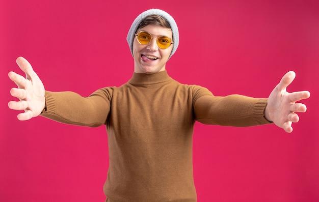 Fröhlicher junger kaukasischer junge in sonnenbrille und mit winterhut, der seine hände ausstreckt