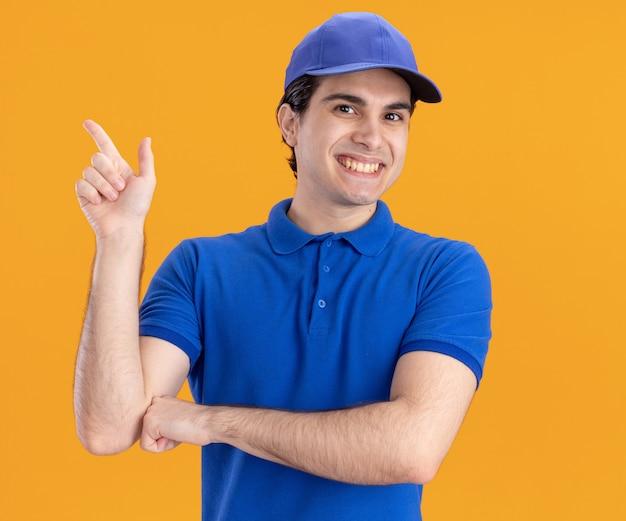 Fröhlicher junger kaukasischer lieferbote in blauer uniform und mütze, die auf die seite zeigt