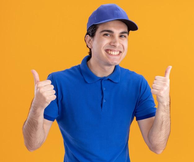 Fröhlicher junger kaukasischer lieferbote in blauer uniform und mütze mit daumen nach oben