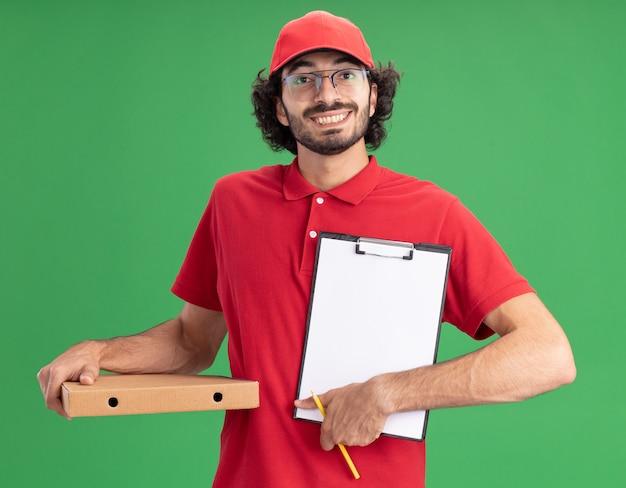 Fröhlicher junger kaukasischer lieferbote in roter uniform und mütze mit brille, die pizzapaket mit bleistift hält und klemmbrett zur kamera zeigt