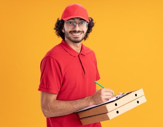 Fröhlicher junger kaukasischer lieferbote in roter uniform und mütze mit brille