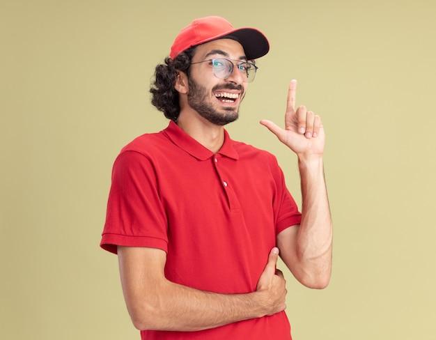 Fröhlicher junger kaukasischer liefermann in roter uniform und mütze mit brille, die isoliert auf olivgrüner wand nach oben zeigt
