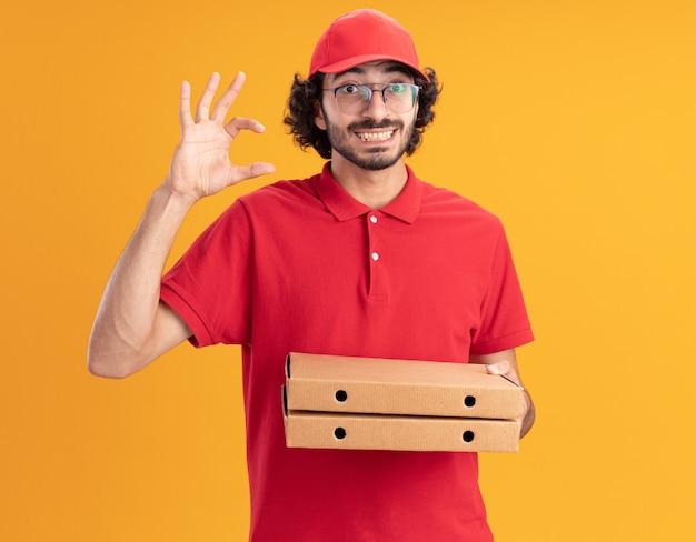 Fröhlicher junger kaukasischer liefermann in roter uniform und mütze mit brille, die pizzapakete hält und kleine gesten einzeln auf oranger wand macht