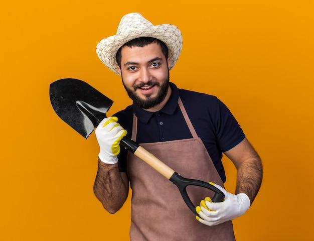 Fröhlicher junger kaukasischer männlicher gärtner mit gartenhut und handschuhen, der spaten isoliert auf oranger wand mit kopierraum hält