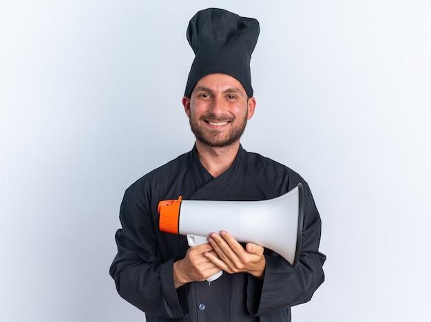 Fröhlicher junger kaukasischer männlicher koch in kochuniform und mütze mit lautsprecher, der die kamera isoliert auf weißer wand betrachtet