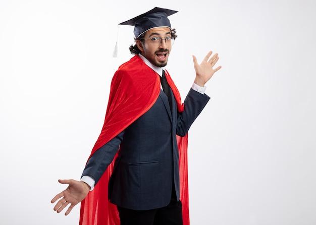 Fröhlicher junger kaukasischer superheldenmann in optischer brille, der anzug mit rotem mantel und abschlusskappe trägt, steht seitlich und hält die hände offen