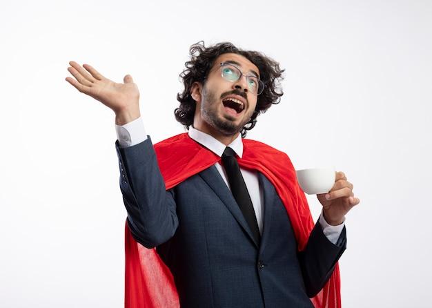 Fröhlicher junger kaukasischer superheldenmann in optischer brille, der anzug mit rotem umhang trägt, steht mit erhobener hand und hält tasse