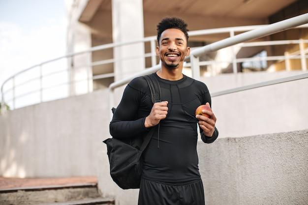 Fröhlicher junger kerl in schwarzem langärmeligem t-shirt und shorts lächelt breit, hält rucksack und apfel, posiert draußen