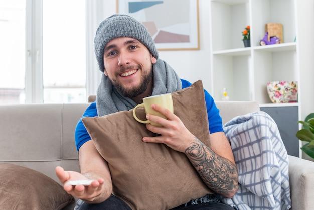 Fröhlicher junger kranker mann mit schal und wintermütze, der auf dem sofa im wohnzimmer sitzt und ein kissen hält, das eine tasse tee hält und nach vorne schaut und eine packung tabletten nach vorne ausstreckt