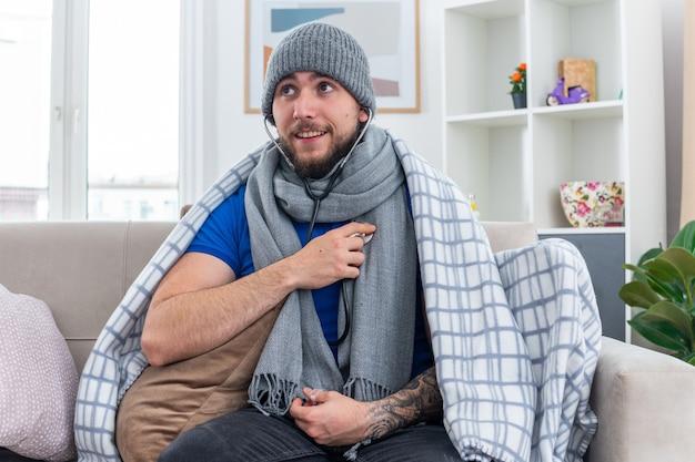 Fröhlicher junger kranker mann mit schal und wintermütze mit in decke gewickeltem stethoskop, der auf dem sofa im wohnzimmer sitzt und seitlich auf seinen eigenen herzschlag hört
