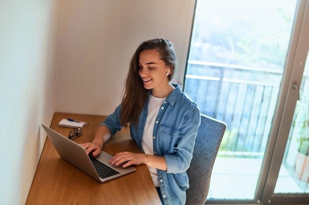 Fröhlicher junger, lässiger, intelligenter, moderner lächelnder mädchenfreiberufler mit drahtlosem kopfhörer mit laptop während der fernarbeit online zu hause