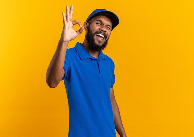 Fröhlicher junger lieferbote blinzelt mit dem auge und gestikuliert auf der orangefarbenen wand mit kopienraum