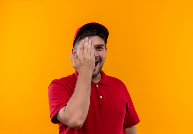 Fröhlicher junger lieferbote in roter uniform und mütze, die ein auge mit einer hand schließen, die breit lächelt