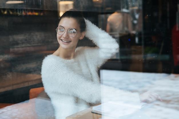 Fröhlicher junger mädchen-freiberufler in einer weißen jacke und brille, der in einem café sitzt und lacht