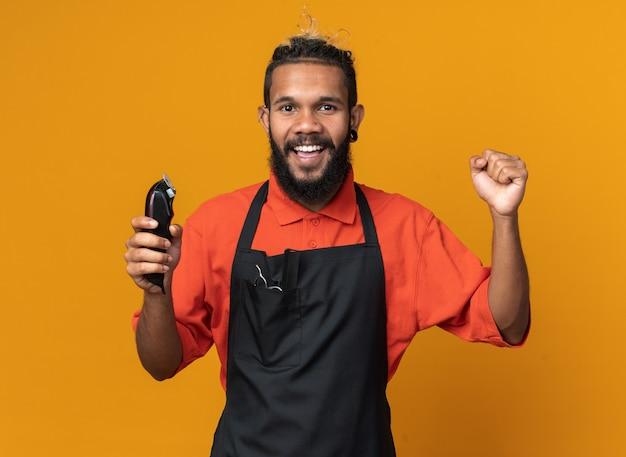 Fröhlicher junger männlicher friseur in uniform, der haarschneidemaschinen hält und nach vorne schaut und die ja-geste isoliert auf oranger wand macht
