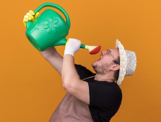 Fröhlicher junger männlicher gärtner mit gartenhut und handschuhen, der sich mit gießkanne isoliert auf oranger wand gießt