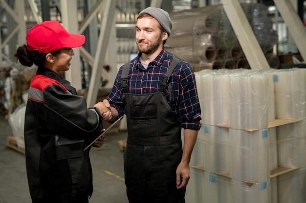 Fröhlicher junger männlicher ingenieur in overalls und kariertem hemd, der seiner kollegin während der arbeit im lager die hand mit digitalem tablet schüttelt
