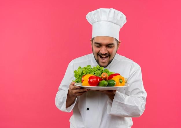 Fröhlicher junger männlicher koch in kochuniform, der einen teller mit gemüse hält und versucht, sie einzeln auf rosa wand mit kopienraum zu essen?